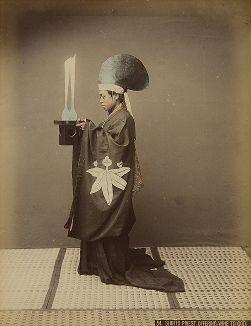 Синтоистский священник с вином для подношения богам. Крашенная вручную японская альбуминовая фотография эпохи Мэйдзи (1868-1912).